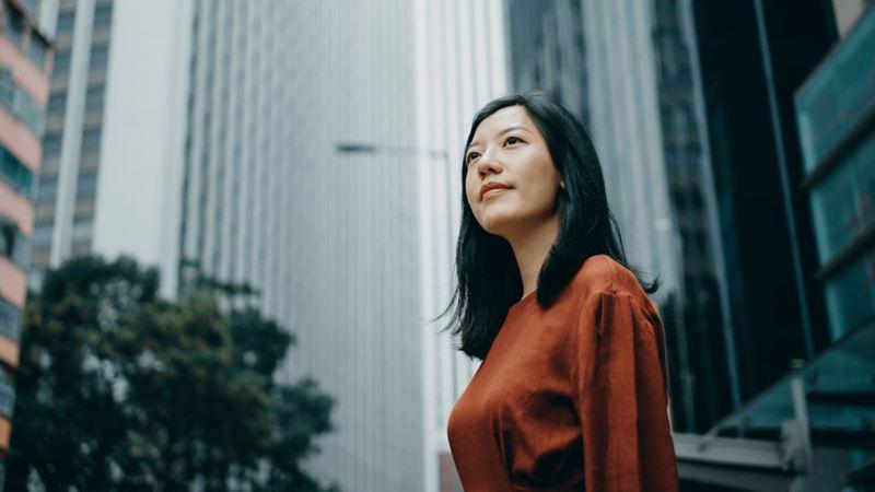 Femme souriant dans un paysage urbain