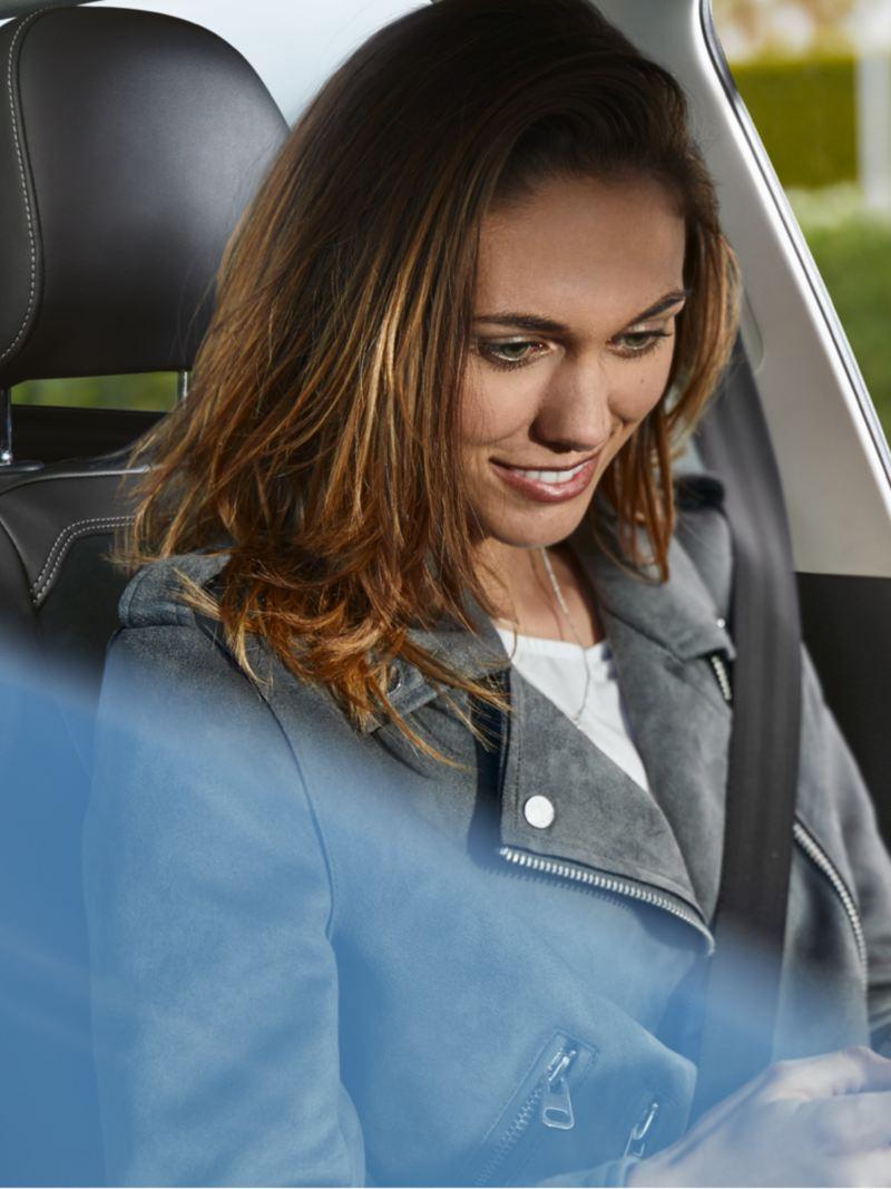 Μια γυναίκα κάθεται στο σταθμευμένο Volkswagen Polo και κοιτά το κινητό τηλέφωνο.