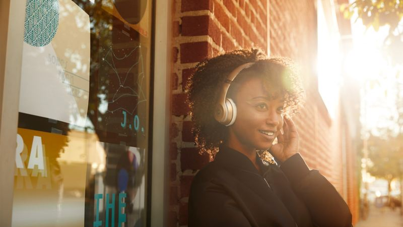 A woman stands in the sunset wearing headphones