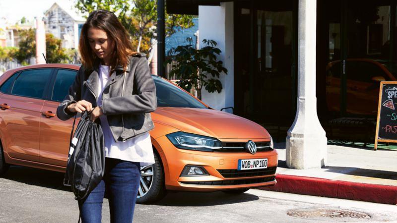 Γυναίκα περπατάει μπροστά από ένα  Volkswagen Polo TGI.