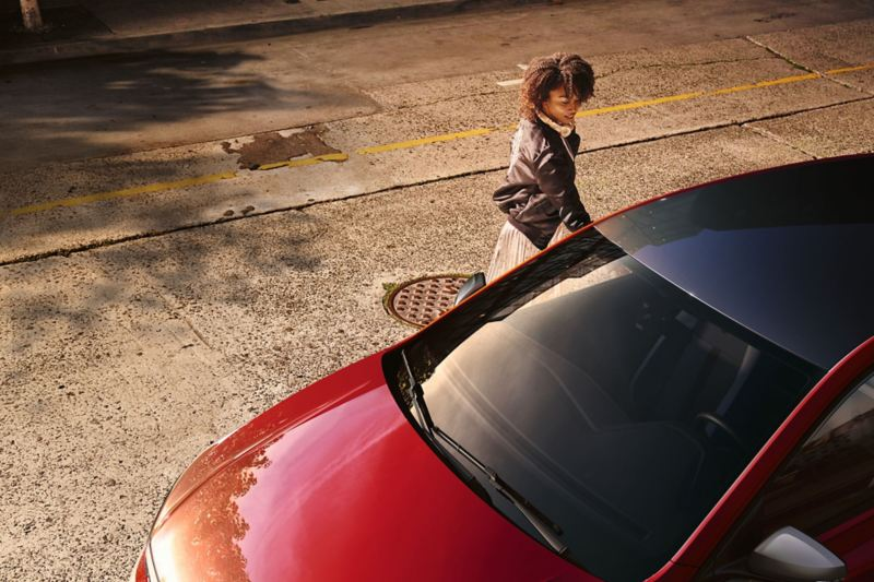 Mulher atrás de um VW Polo beats na estrada com uma faixa decorativa autocolante.