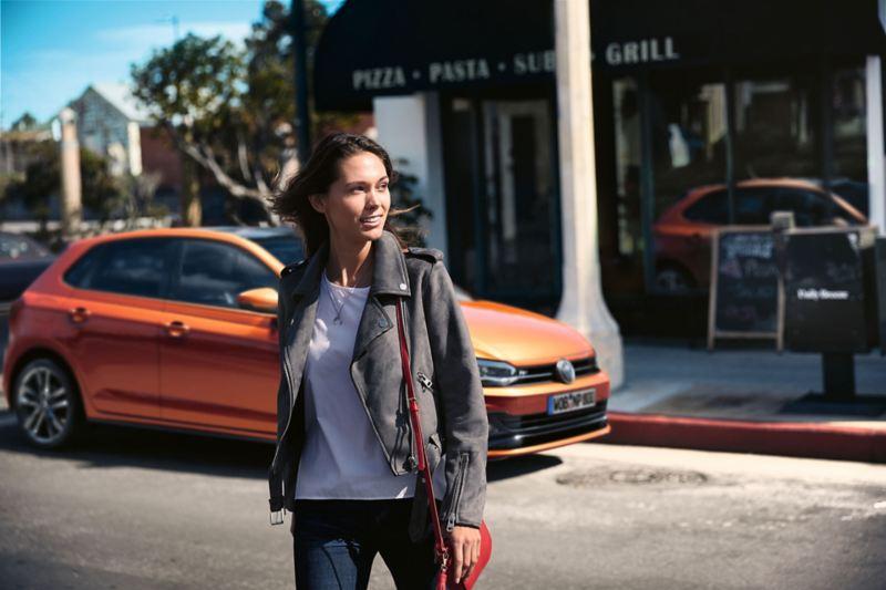 Μια γυναίκα διασχίζει τον δρόμο, στο παρασκήνιο ένα σταθμευμένο Volkswagen Polo TGI.