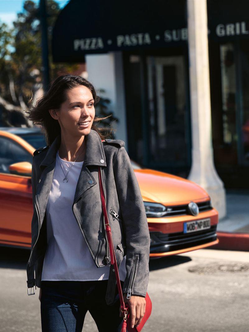 eine Frau geht über die Straße, im Hintergrund ein eingeparkter VW Polo
