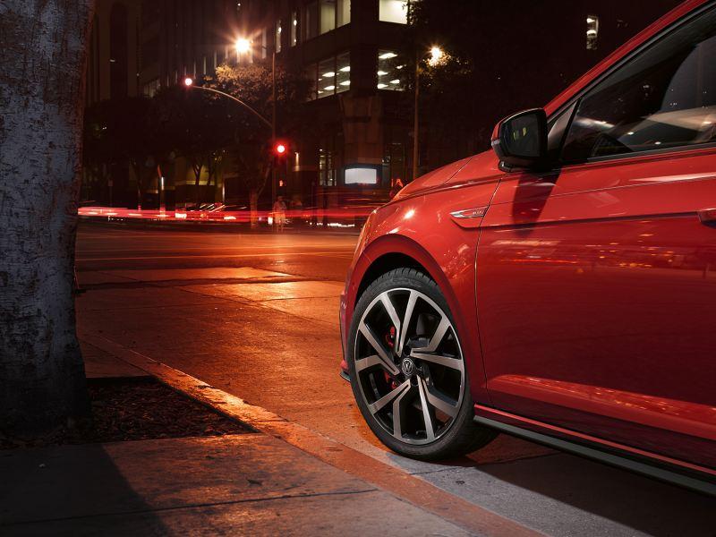 Particolare sul cerchio di Volkswagen Polo GTI rossa parcheggiata di notte