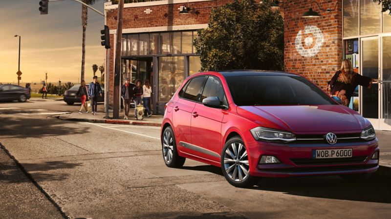 VW Polo beats on the side of the road in front of building with people strolling by