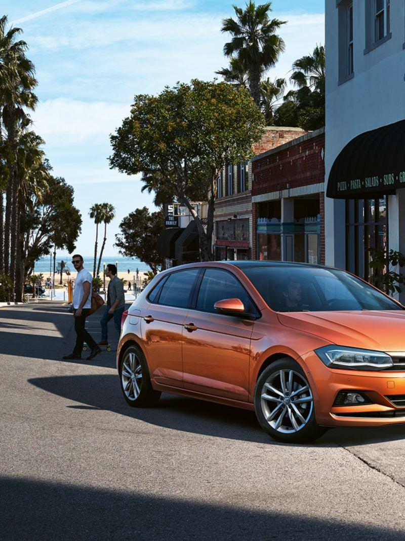 Oranssi Volkswagen Polo kuvattuna aurinkoisella kadulla ravintolan edustalla