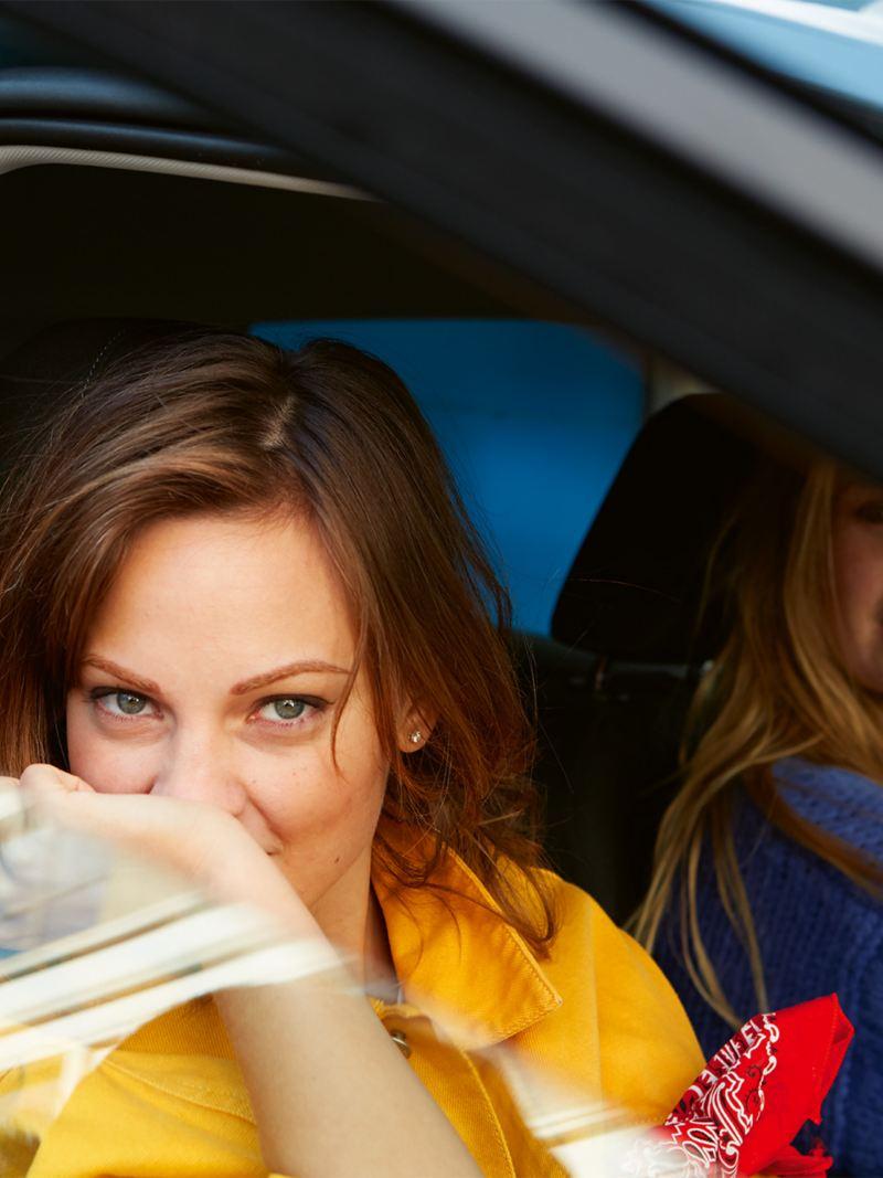Deux femmes sont assises à l'avant d'une Polo IQ.DRIVE.