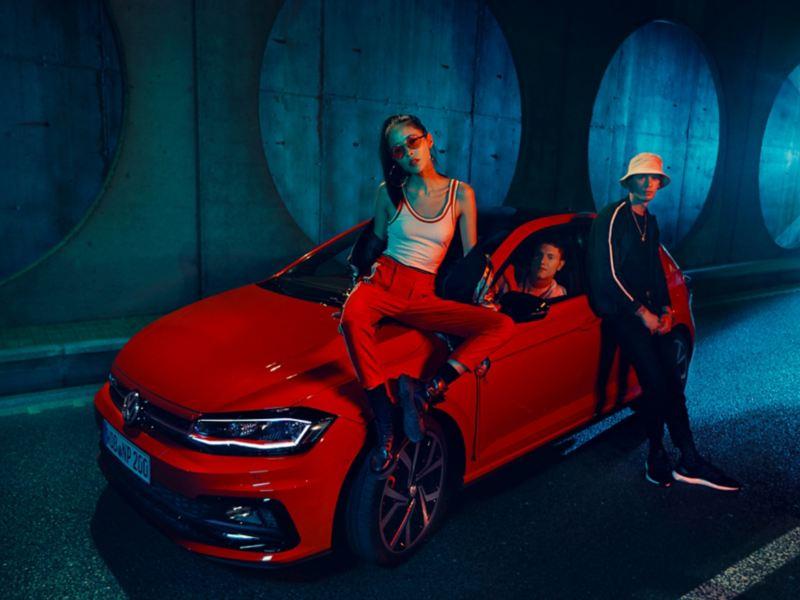 Ragazzi appoggiati su Volkswagen Polo GTI rossa di notte