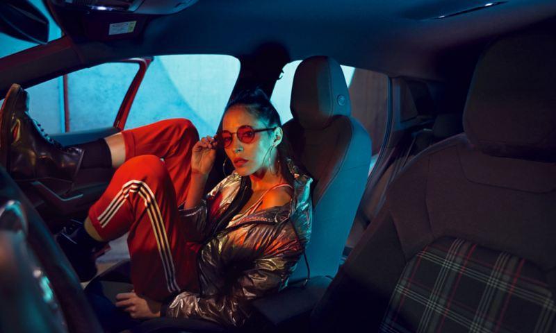 Donna sportiva appoggia le scarpe sulla cruscotto all'interno di Volkswagen Polo GTI