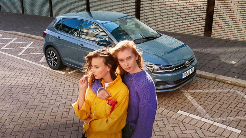 VW Polo IQ. Drive parkt, Frau steigt aus dem Wagen, andere Frau im Vordergrund