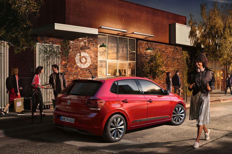 """Vista traseira de um VW Polo beats em frente a um passeio movimentado e um edifício com o logótipo """"beatsaudio""""."""