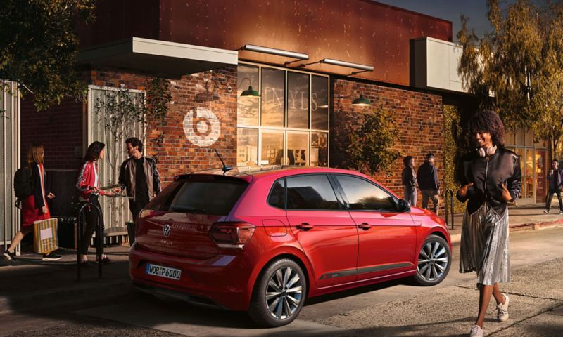 "View of the rear of VW Polo betas on the side of the road with bustling sidewalk und building with ""beatsaudio"" -Logo"