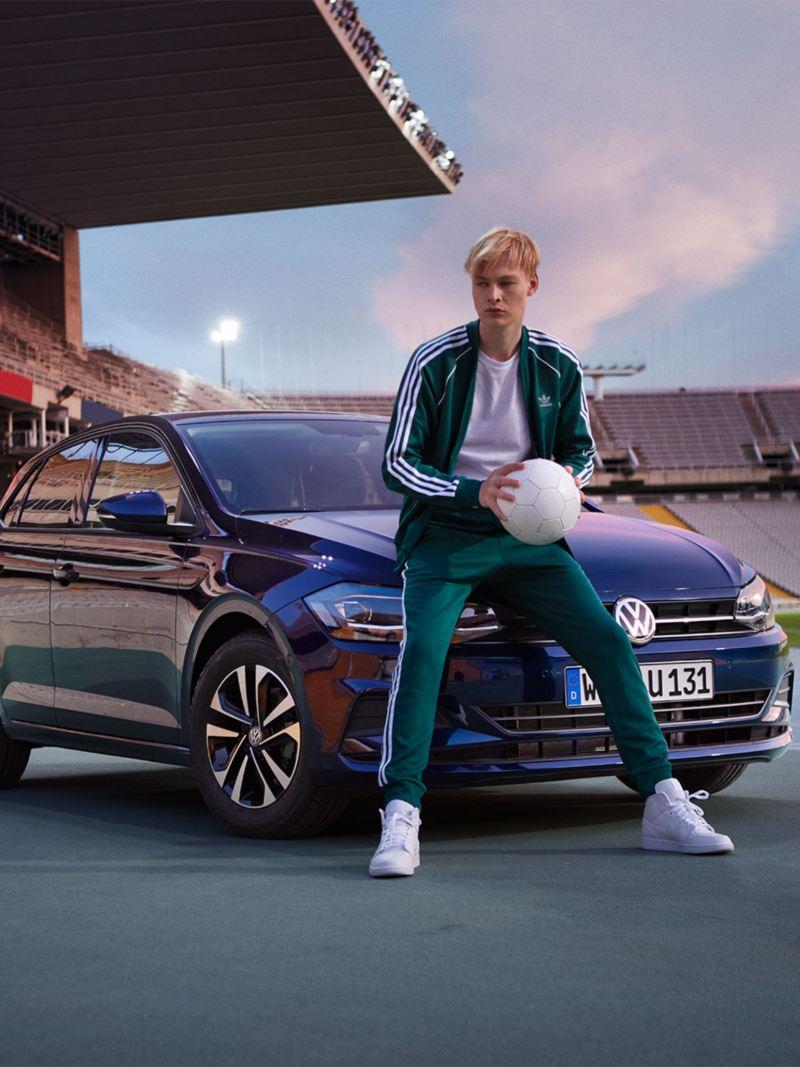 VW-Polo UNITED in Stadion, Mann posiert auf Motorhaube mit Ball