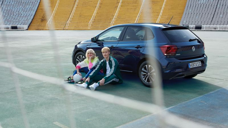 Man and woman in front of VW Polo United 3/4 rear, view through football goal mesh