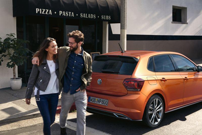 coppia abbracciata cammina dietro a Polo Volkswagen