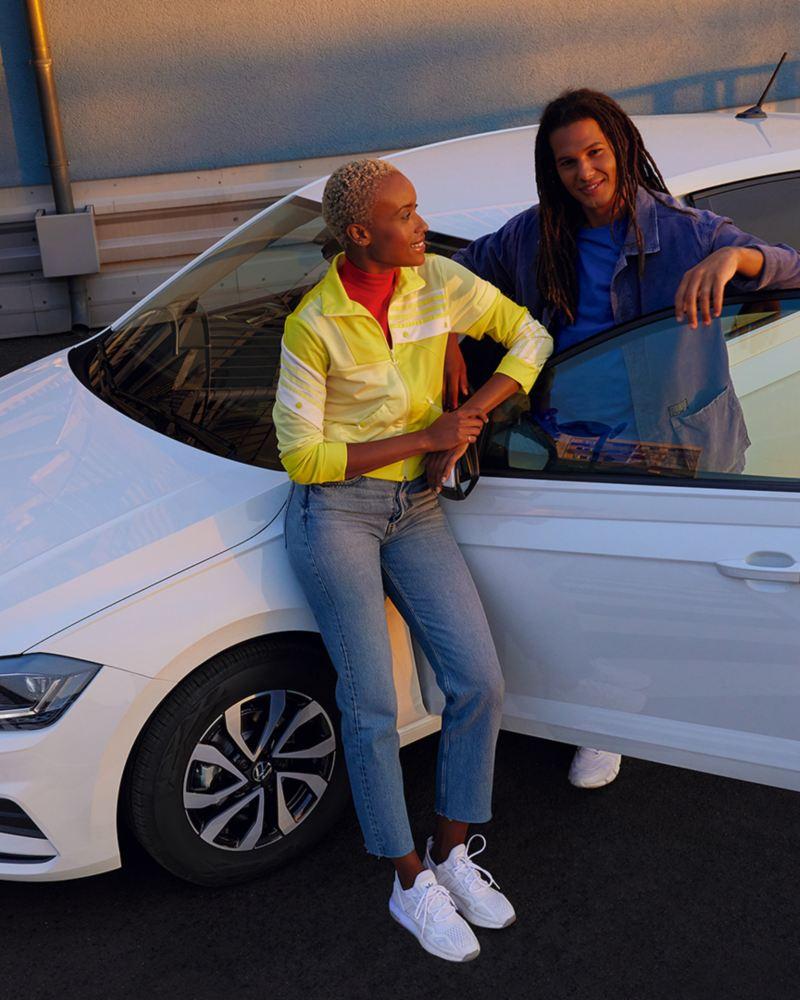 VW Polo ACTIVE blanche avec une porte ouverte dans un parking urbain. Vu d'un angle d'en haut, avec vue sur le capot, le toit et le côté.