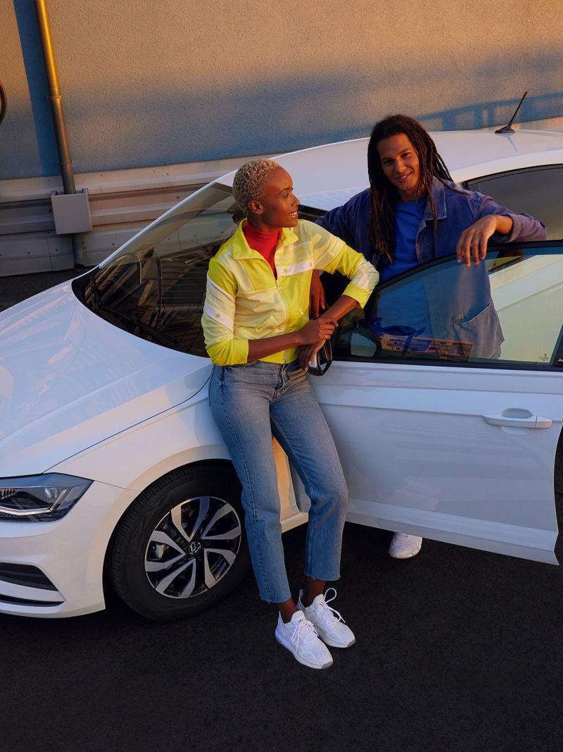 Weißer VW Polo ACTIVE mit geöffneter Tür auf einem urbanen Parkplatz. Blick von schräg oben auf Motorhaube, Dach und Seite.