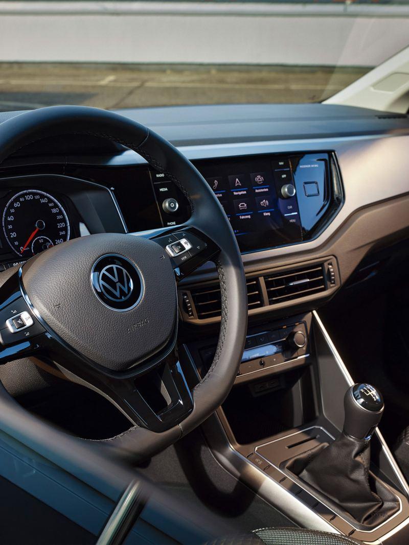 Weißer VW Polo ACTIVE von innen im Cockpit. Blick durchs Fenster auf Multifunktionslenkrad und Armaturen.