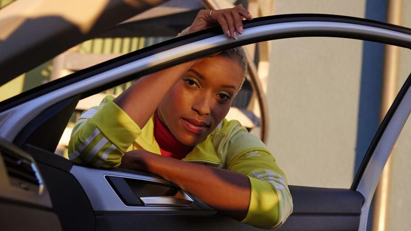 Weißer VW Polo ACTIVE. Blick von innen durch geöffnete Tür und Fenster auf Frau.