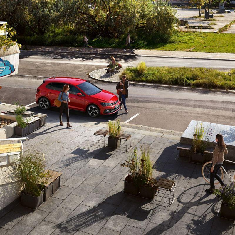 Parkender Volkswagen vor einem Platz, zwei Leute am Auto