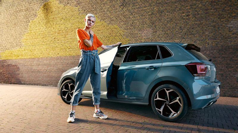 Une jeune femme se tient devant la version R-Line de la Polo IQ.DRIVE.