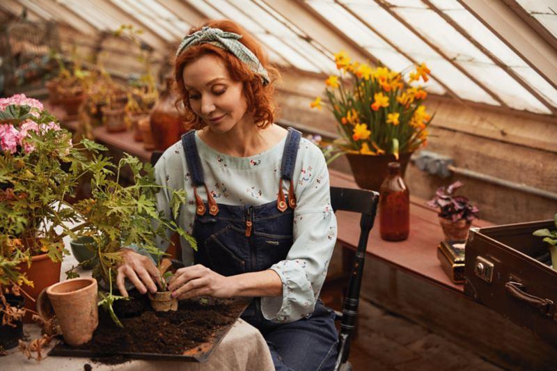 Linda Schilén planterar växt i kruka