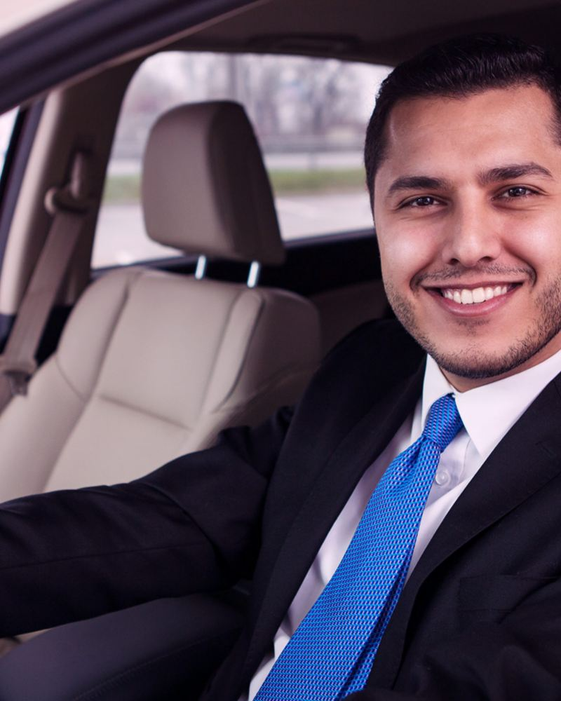Joven sonriente al volante de un auto nuevo adquirido con My Leasing de Servicios Financieros Volkswagen