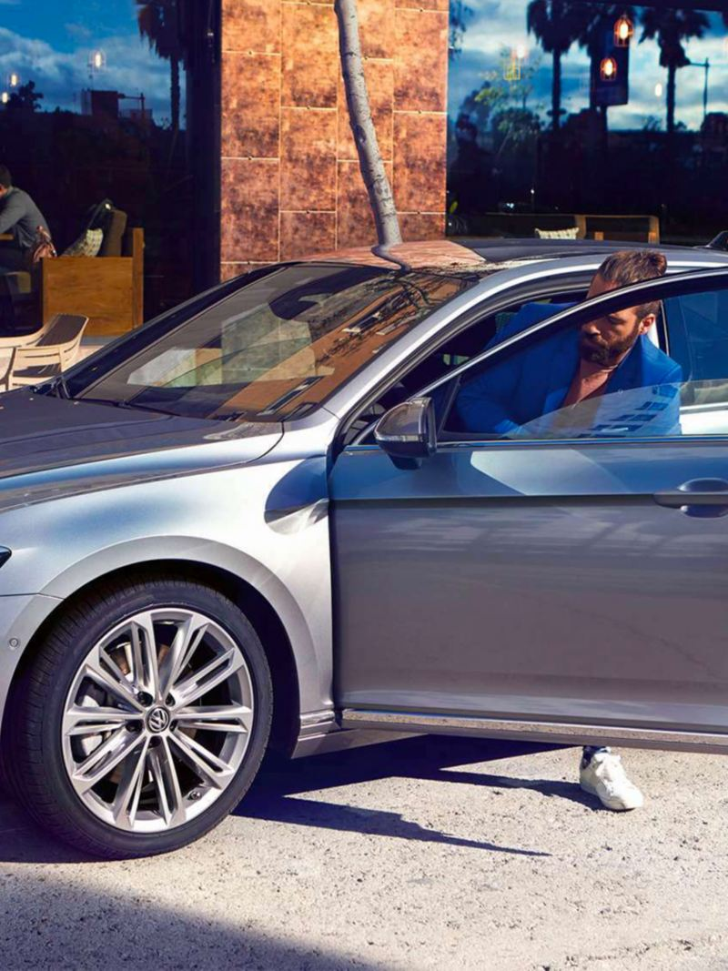Un ragazzo entra nella sua auto Volkswagen Passat