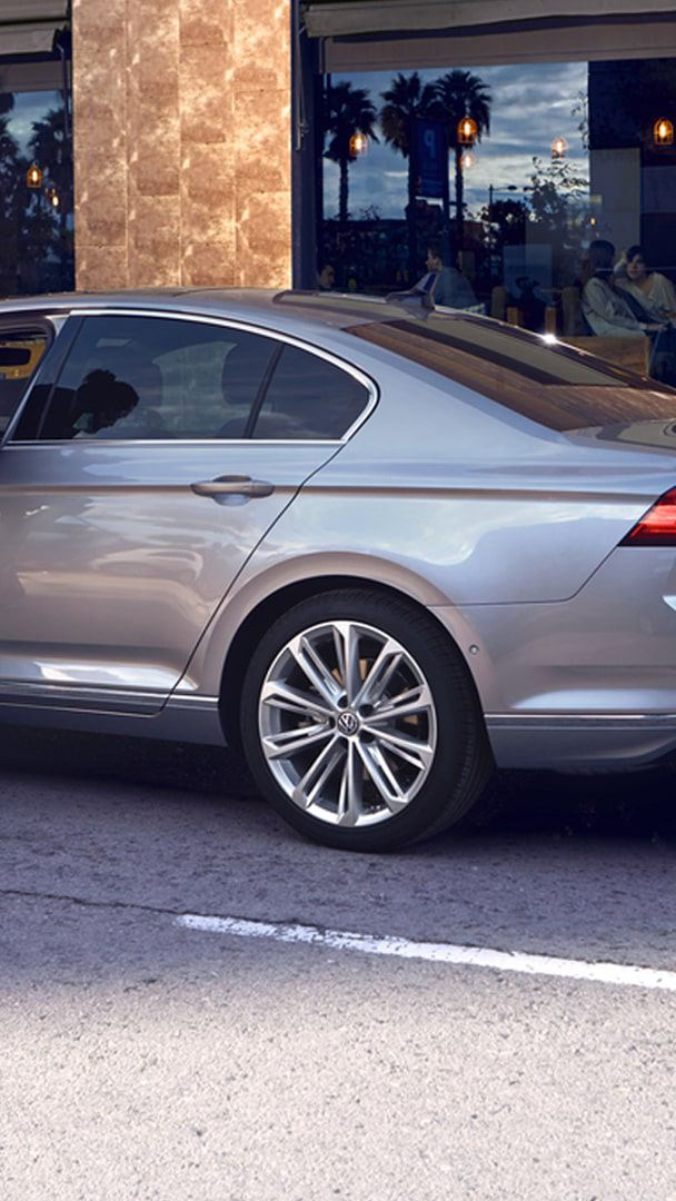 "Passat limousine Elegance in pyrite-silver with wheel ""Verona"", side-front standing, man gets out of the car"