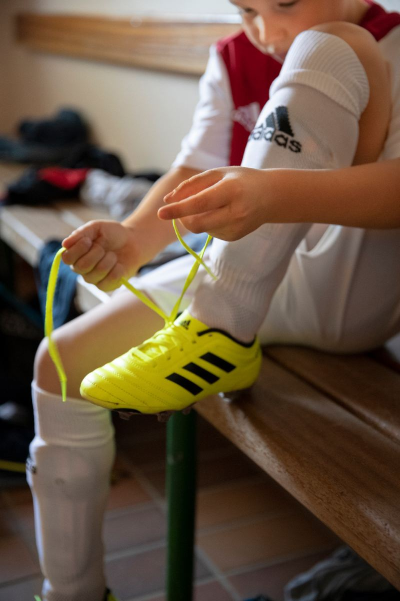Kleiner Kicker schnürt seine Fußballschuhe.