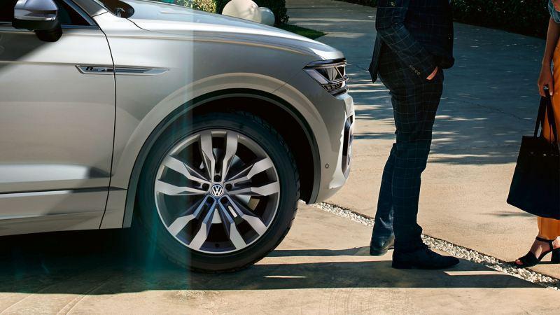 Un couple est en train de discuter devant une Volkswagen, le véhicule est équipé de pneus été