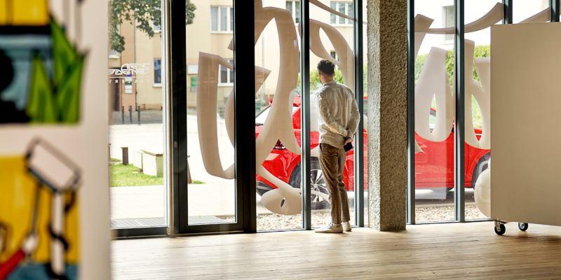 """Blick aus der Galerie """"Brain Damage"""" nach draußen auf die Straße, vor der Tür steht der Polo"""