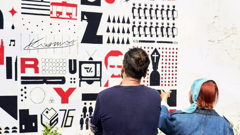 Cezary und Frau betrachten ein Mural