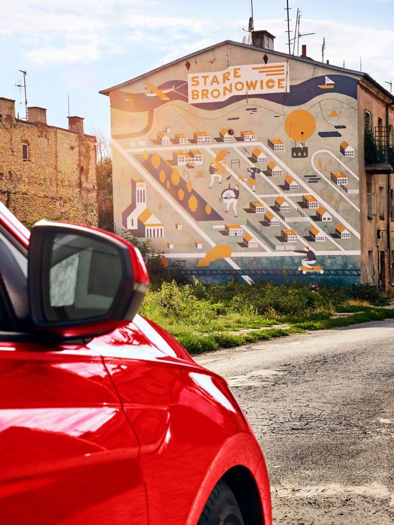 VW Polo schräg von hinten geschossen, im Hintergrund Häuserwand mit Street Art Gemälde