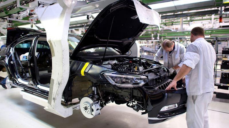 Zwei Volkswagen Mitarbeiter bei der Montage der Frontpartie eines Passat