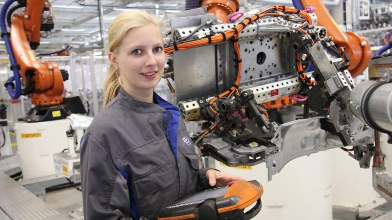 Eine Volkswagen Mitarbeiterin hält ein Bedien-Display eines Montage-Roboters in der Hand