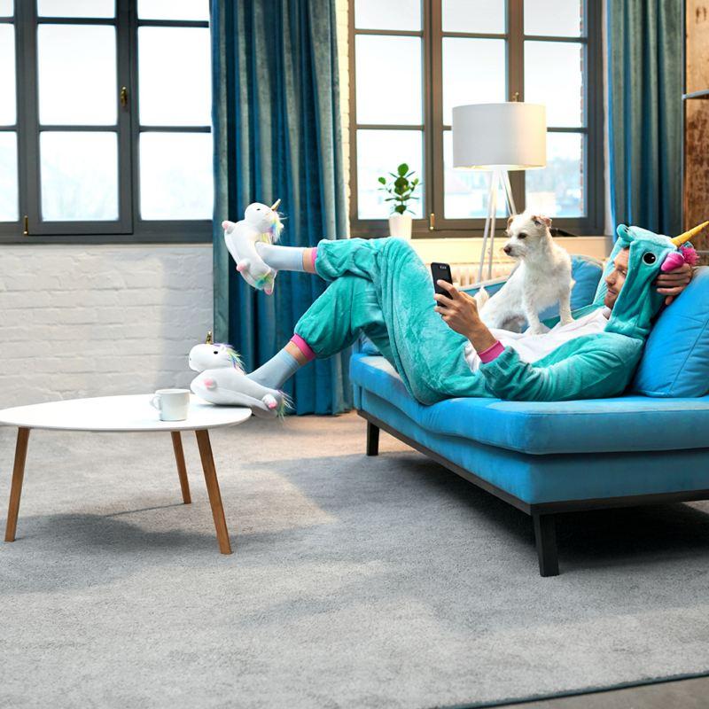 Ein Mann im Einhornkostüm liegt auf seinem Sofa und schaut auf sein Handy.