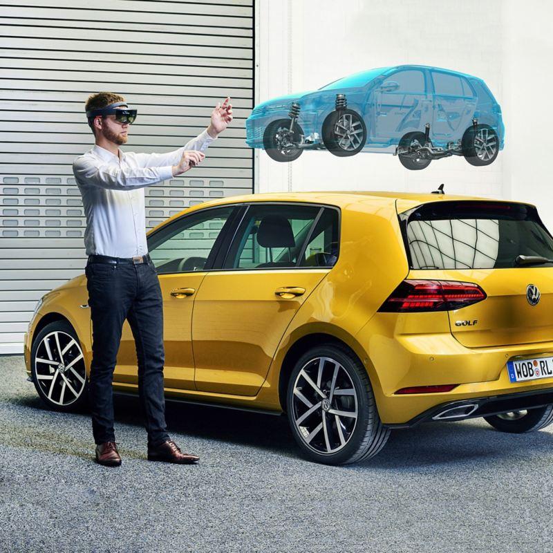 Mann mit Virtual Reality Brille neben einem VW Golf, neben sich das Bild eines virtuellen Fahrzeugs in der Luft