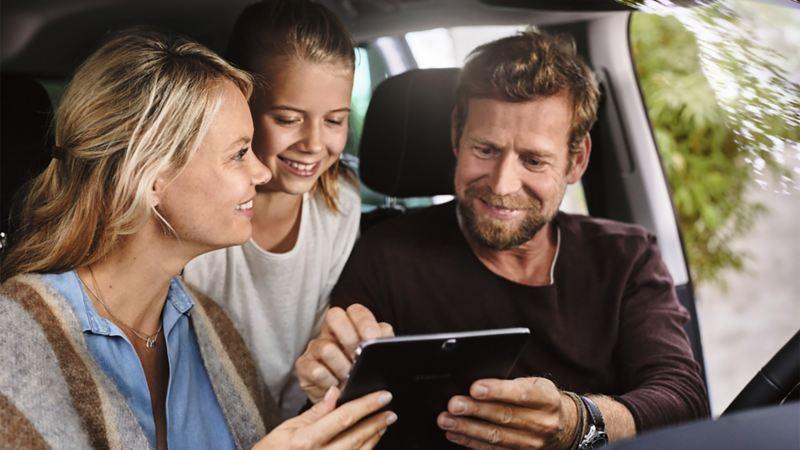 Padre e madre usano un tablet con la figlia.