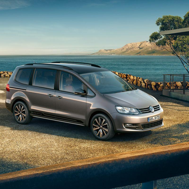 """VW Sharan mit """"Black Style""""-Schriftzug als seitliche Folienbeklebung parkt vor einem Haus am Meer."""
