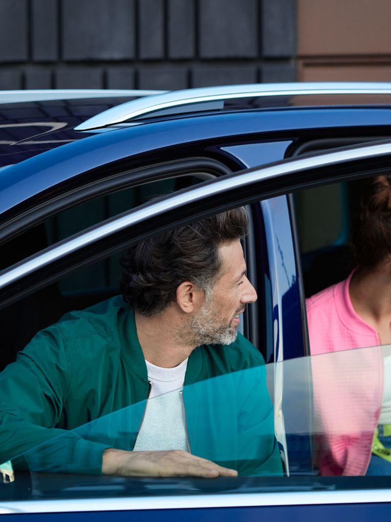 Mann und Frau im VW Sharan UNITED blicken aus dem Fahrzeug nach links hinten