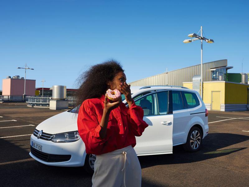 Weißer VW Sharan ACTIVE steht mit geöffneter Tür auf einem urbanen Parkplatz. Frau mit rotem Hemd davor.