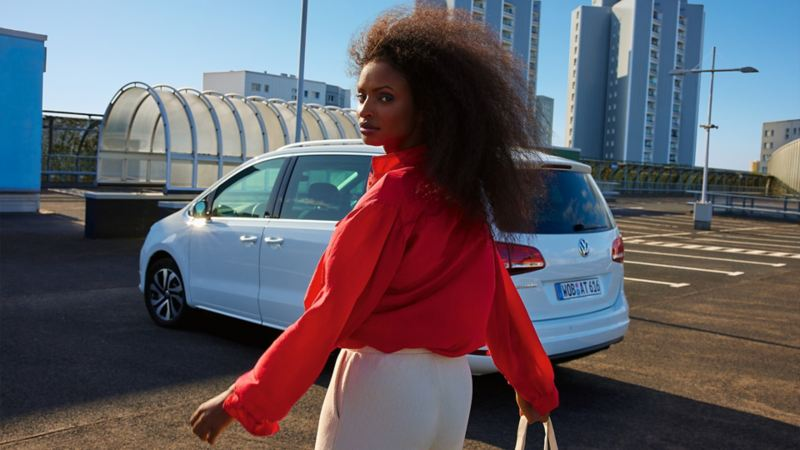 Weißer VW Sharan ACTIVE auf einem urbanen Parkplatz. Blick auf Kofferaum und Seite. Frau mit rotem Hemd davor.