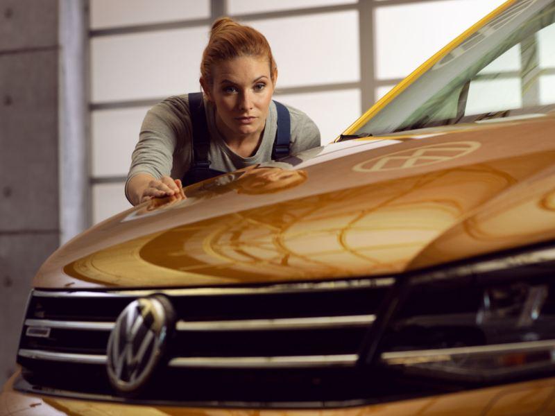Technicienne Volkswagen vérifiant la carrosserie d'un utilitaire