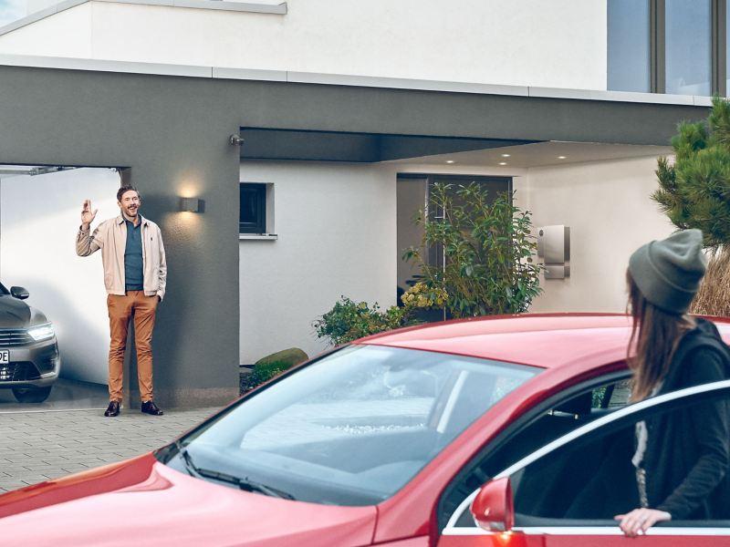 Der Vater verabschiedet sich von seiner Tochter, die in den roten VW Passat B6 steigt – VW Vorgängermodelle