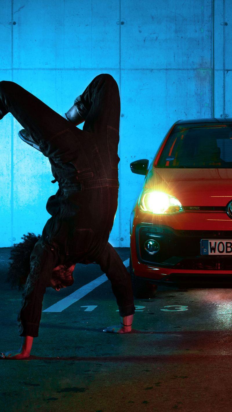 Client Volkswagen en train de faire le poirier devant une Volkswagen dont les phares sont allumées