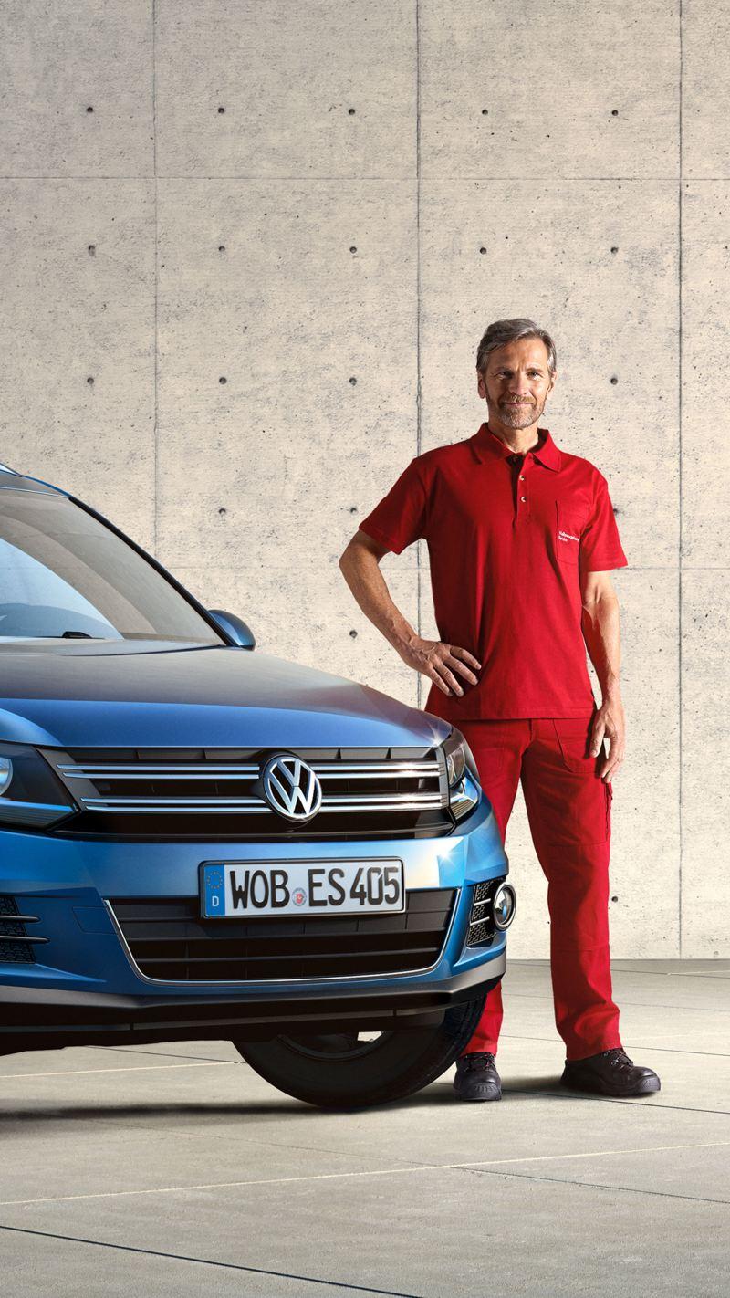Uomo di fianco a Volkswagen blu