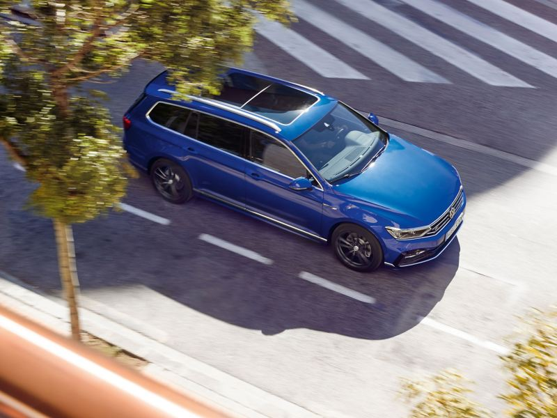 A blue VW car with Volkswagen Accessories products is driving on the road – Volkswagen Exterior