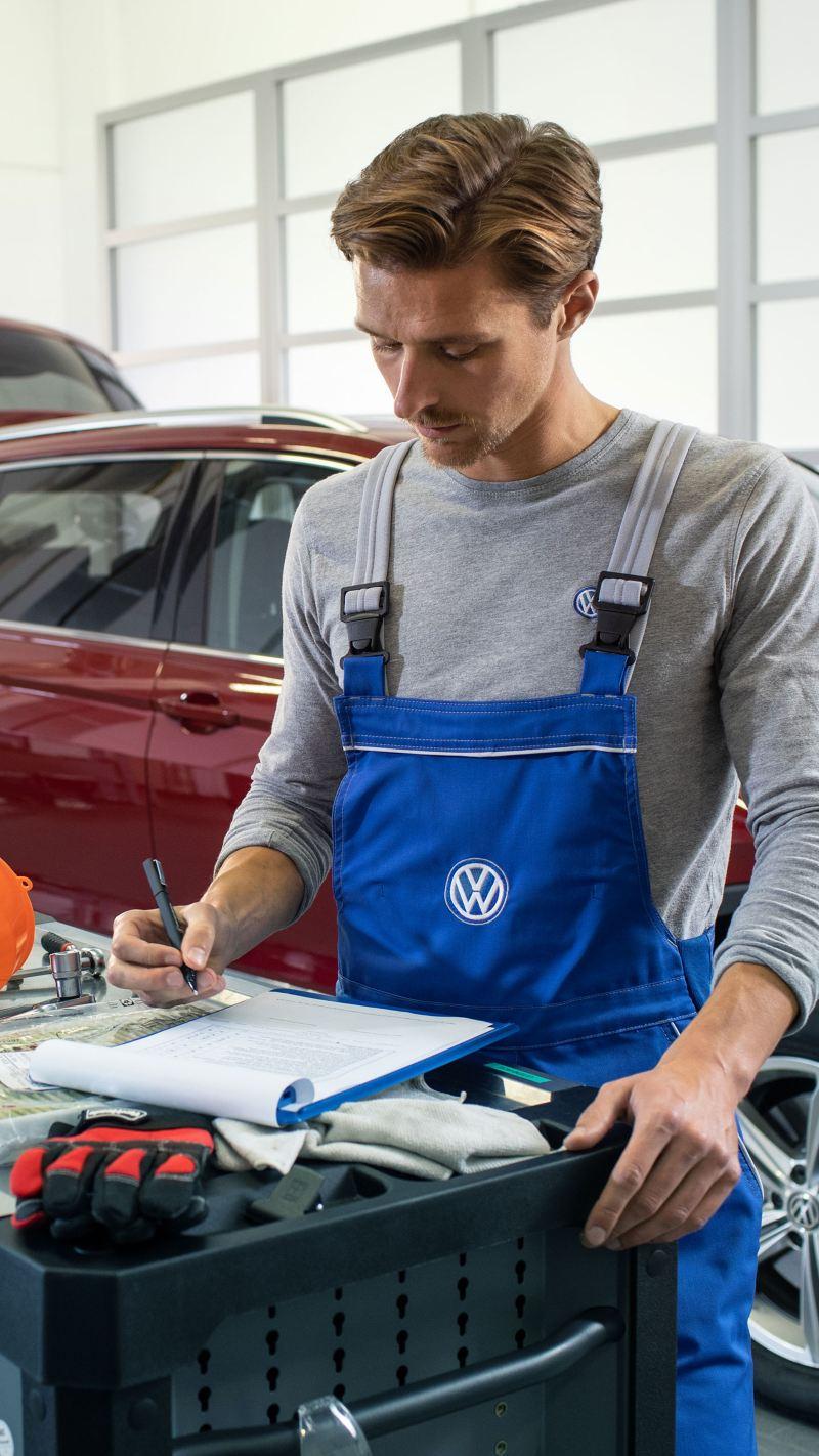 Employé de service VW devant une Volkswagen rouge avec moteur diesel et capot ouvert dans un atelier
