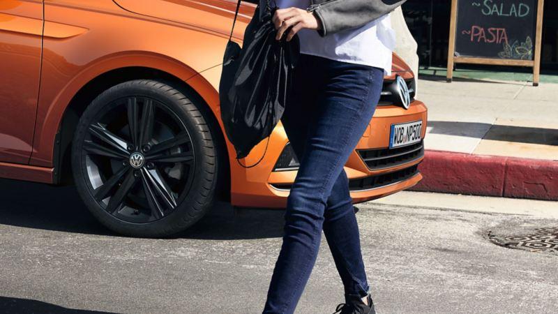 Donna cammina davanti a Volkswagen Polo in sosta
